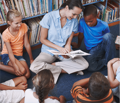 Adult in Library Reading Book to Children